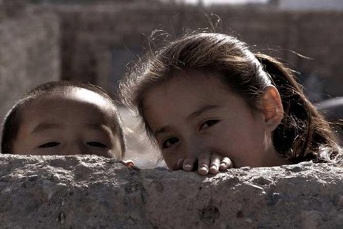 дети выглядывают из-за стены