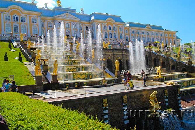 Люди расматривают фонтаны Петергофа