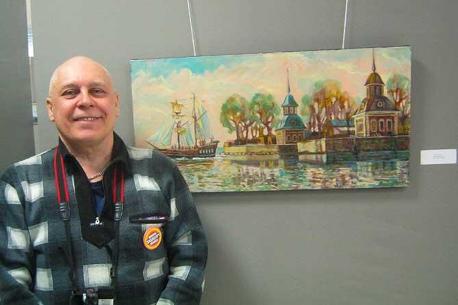 Алексаей Дадашев на фоне своей картины