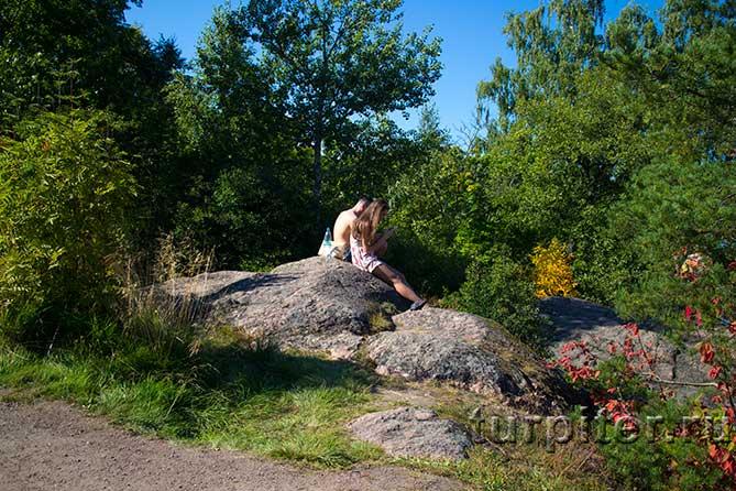 девушка и парень сидят на камне