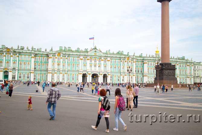 туристы расматривают Александровскую колонну